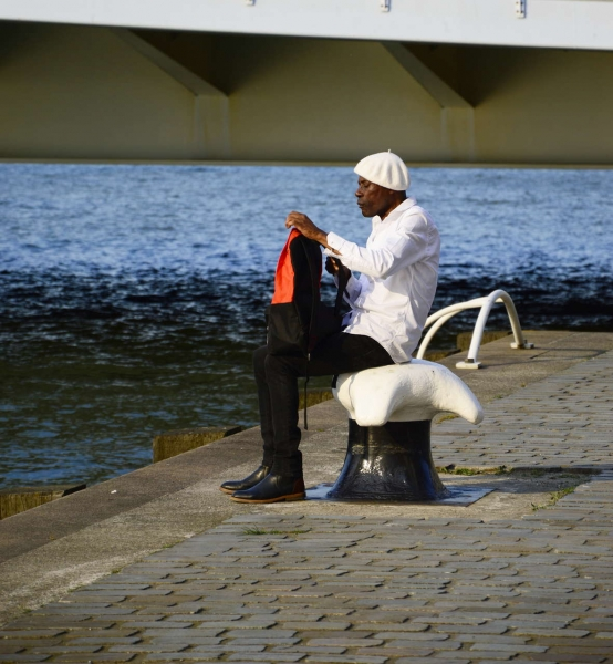 The pic was taken in Rotterdam, Zone Blaak. This man seemed to really enjoy himself, sitting in front of the water, enjoying the sun. I liked his style and his very orange backpack caught my attention, with the blue water on the other side.